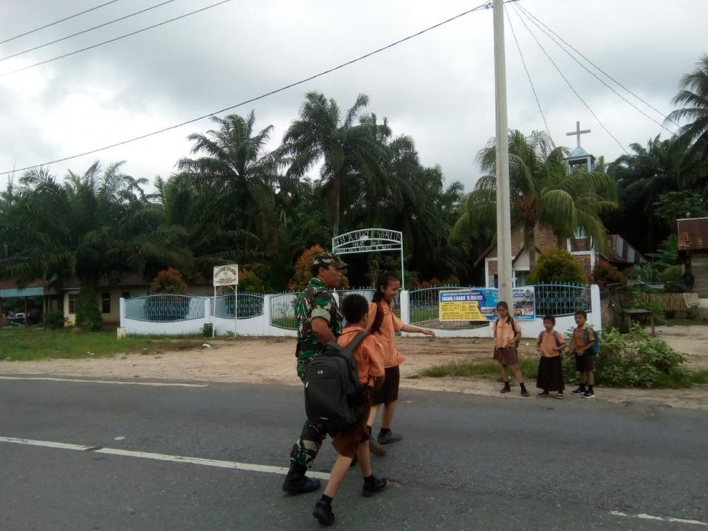 Arus Lalin Cukup Padat dan Rawan, Babinsa Seberangkan Anak Sekolah