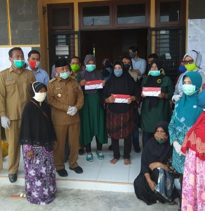 Bupati Pelalawan Serahkan Bantuan Sembako Dari TP PKK Kabupaten Pelalawan  Kepada Warga Di Kecamatan Langgam