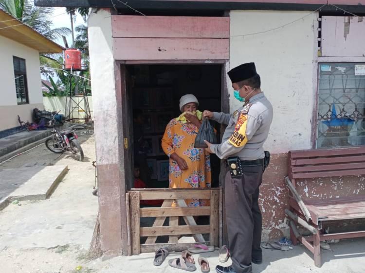 Bhabinkamtibmas Polres Kuansing keliling kampung berbagi Daging Kurban