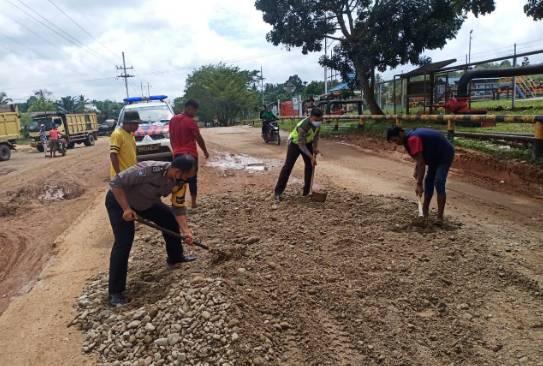 Tak Kunjung Diperbaiki, Anggota Polsek Tapung Hulu Dibantu Warga Timbun Jalan yang Rusak Parah
